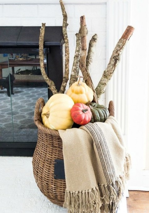 a cool modern fall display with a tall basket, a blanket, branches and colorful pumpkins