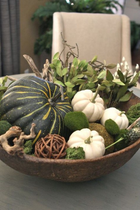 a wooden bowl with natural pumpkins, moss balls, vine balls, foliage and some branches