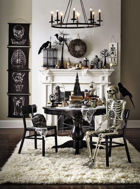 a fantastic black and white Halloween scene with signs, faux birds, skeletons, bottles, candles and a candle chandelier