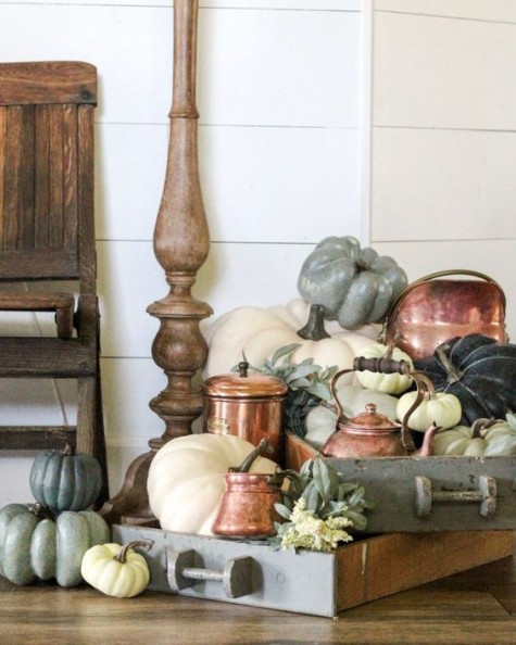 a farmhouse display with vintage drawers, copper teaware and colored pumpkins