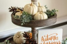 17 a wooden stand with eucalyptus, white and orange pumpkins and pinecones and a small sign