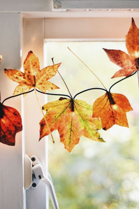 a fall leaf garland with lights is a whimsy and veyr cute fall decoration for your window, it will fill the space with glow