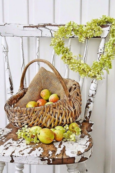 a harvest themed fall display with a greenery wreath and a basket with burlap and apples