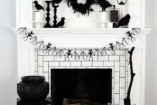 19 a Halloween fireplace with a bat bunting, a blakc feather wreath, blackbirds, candle lanterns, a cauldron and a broom