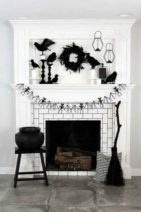 a Halloween fireplace with a bat bunting, a blakc feather wreath, blackbirds, candle lanterns, a cauldron and a broom