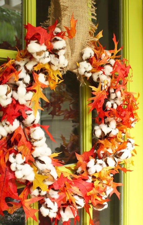 a fall wreath with bright fall leaves, cotton and a burlap ribbon to hang it is a very creative idea to try