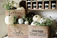 19 place fresh white pumpkins and faux dark ones into craes and add greenery to create a truly fall display