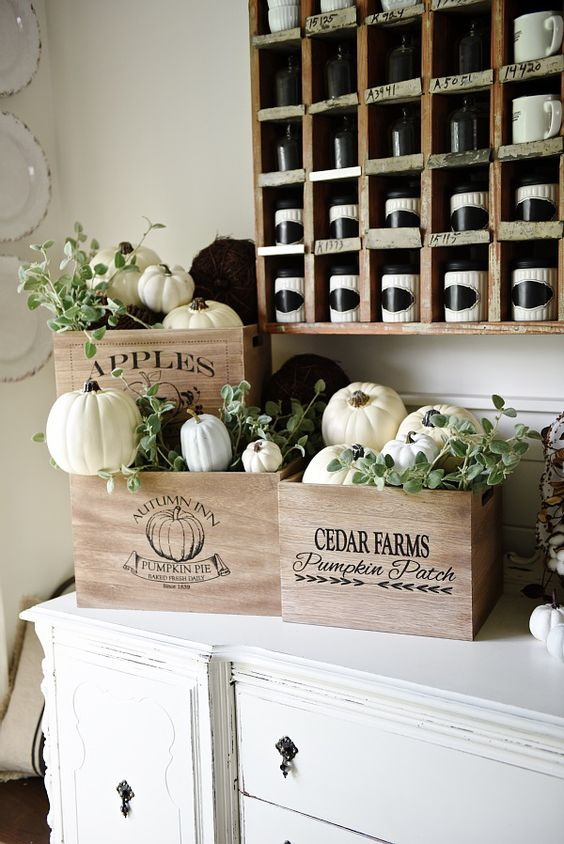 place fresh white pumpkins and faux dark ones into craes and add greenery to create a truly fall display