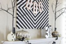 20 a large geo sign with a BOO banner, a bat banner, various pumpkins, branches and numbers for a stylish minimal mantel