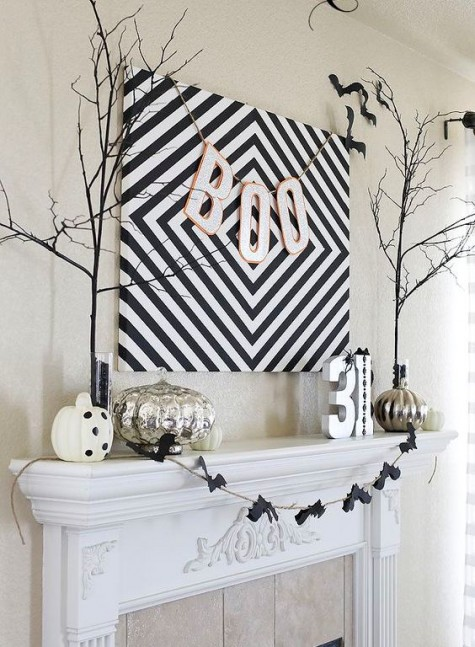 a large geo sign with a BOO banner, a bat banner, various pumpkins, branches and numbers for a stylish minimal mantel