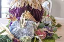 21 a bright arrangement of jewel tone velvet pumpkins with feathers and beads placed on a moss sheet