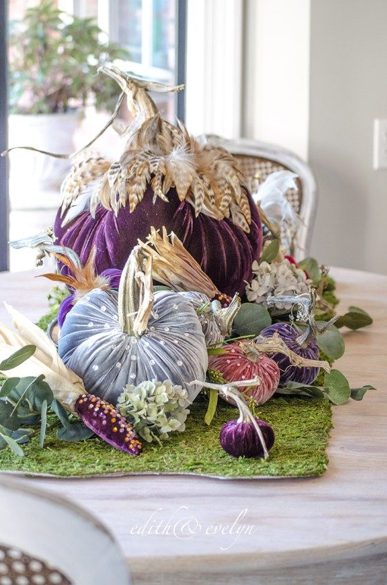 a bright arrangement of jewel tone velvet pumpkins with feathers and beads placed on a moss sheet