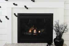 21 a monochromatic fireplace with black bats, blackbirds, busts and candles is a timelessly stylish idea for Halloween
