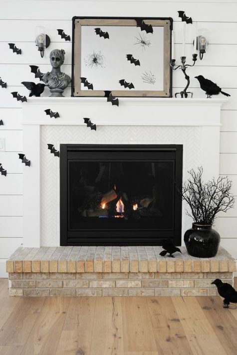 a monochromatic fireplace with black bats, blackbirds, busts and candles is a timelessly stylish idea for Halloween