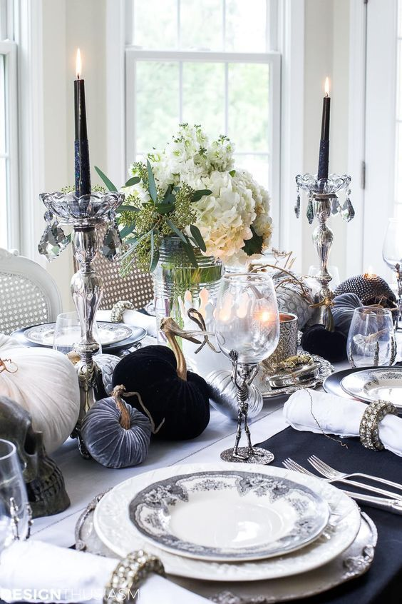 a monochromatic tablescape with black candles, black, white and grey fabric pumpkins, elegant porcelain and glasses with skeletons