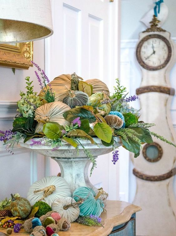 a bright velvet pumpkin arrangement with faux greneery, blooms and foliage in a vintage stone urn