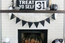 23 a simple and monochromatic Halloween mantel with signs, black and white pumpkins, a black bunting and firewood