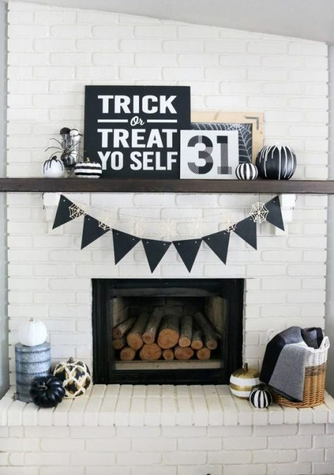 a simple and monochromatic Halloween mantel with signs, black and white pumpkins, a black bunting and firewood