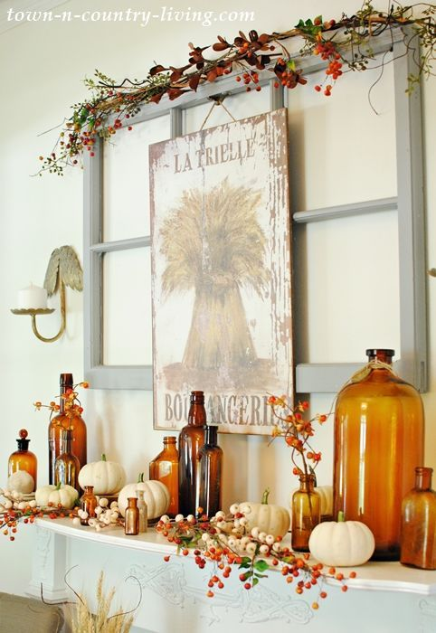 a bright fall mantel with amber bottles, berries and white pumpkins, a sign and some branches