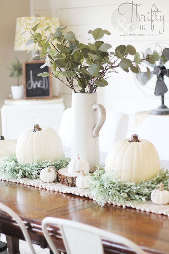 a fall centerpiece of greenery, white pumpkins of various sizes and wood slices