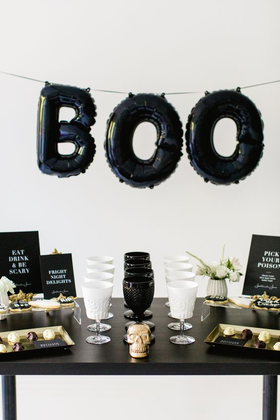 a stylish black and white dessert table for a Halloween party with a balloon garland, glasses, blooms and signs
