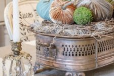 25 a unique arrangement of velvet pumpkins and moss balls palced on a pillow of hay and a vintage metal stand