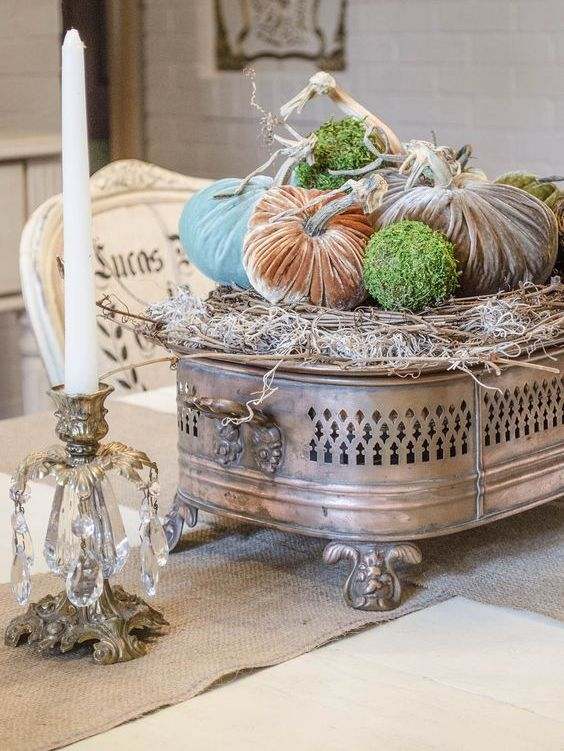 a unique arrangement of velvet pumpkins and moss balls palced on a pillow of hay and a vintage metal stand