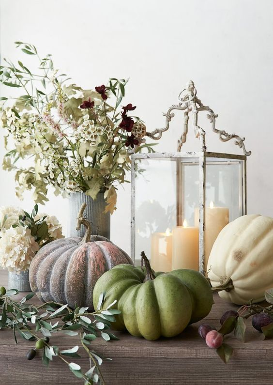 a catchy fall display with heirloom pumpkins, a vintage candle lantern, neutral blooms and greenery