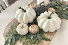 26 a wooden cutting board with greenery and fake pumpkins in white, gold and dark green as a fall centerpiece
