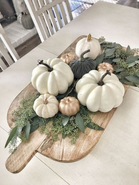 a wooden cutting board with greenery and fake pumpkins in white, gold and dark green as a fall centerpiece