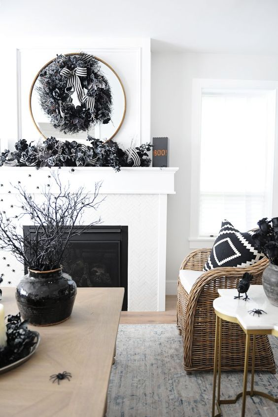 stylish black and white Halloween decor done with fabric garlands and a wreath, black branches in a vase and some blackbirds