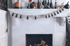 a Halloween mantel and a fireplace with orange pumpkins, black and orange candles and a pumpkin in a cloche