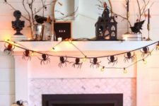 a Halloween mantel and fireplace with a spider bunting, lights, pumpkins, lanterns and candles