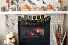 a Halloween mantel with pumpkins, bats, fall leaves, candles and a crate with natural pumpkins