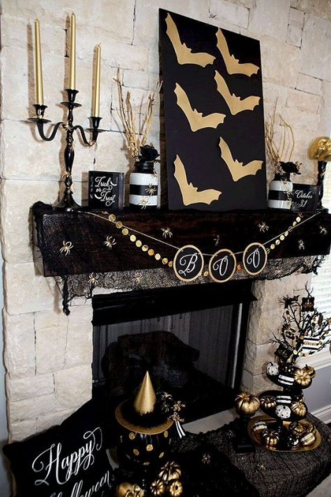a black and gold mantel with bats, a bunting, candles, striped jars with branches, painted pumpkins and a pillow