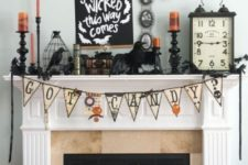 a bold Halloween mantel with bats, a bunting, a cage with a blackbird, candles, a clock and a sign