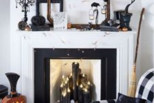 a bold Halloween mantel with black candles, lights, a black tree, glam embellished pumpkins and a bunting