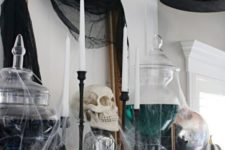 a bold Halloween mantel with black tille, a witch hat, black and white oumpkins and witches' brew in jars