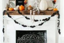 a bright Halloween mantel with a bat bunting, natural and painted pumpkins, a skeleton, black balloon letters and a sign