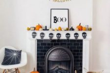 a bright mantel with orange and gold pumpkins, a skull bunting, candles and a sign plus a bat bunting over the mantel