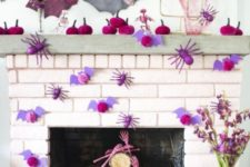 a bright pink Halloween mantel with lots of paper spiders, bats, pumpkins and skeleton hands