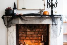 a chic Halloween mantel with candles, bottles, a witch hat, black tulle, natural pumpkins and blooms in a cauldron