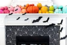 a fireplace filled with eyeballs, decorated with bats and a mantel with colorful pumpkins for a fun and whimsy look