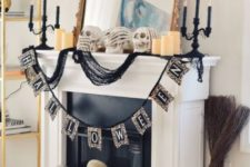 a glam Halloween mantel with a large mirror, black candleholders, a bunting and lots of skulls