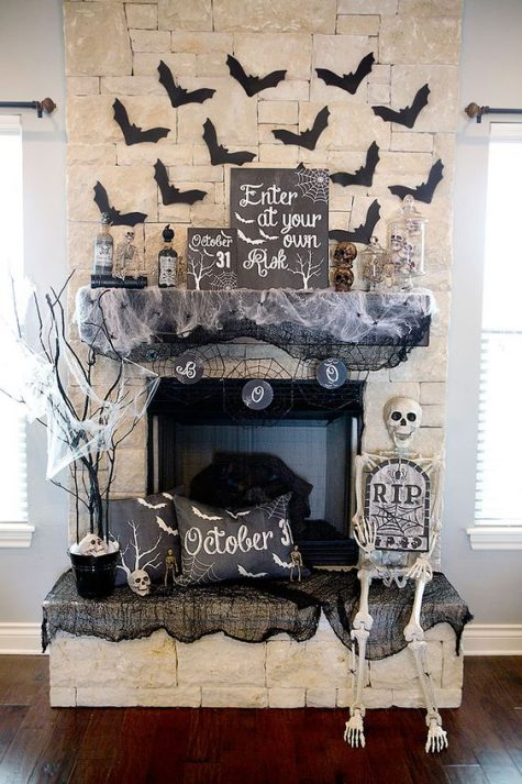a monochromatic Halloween mantel and fireplace with a skeleton, bats, signs, pillows, spiderwebs