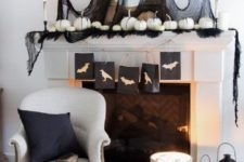a monochromatic Halloween mantel with black tulle, feathers, white pumpkins and candles