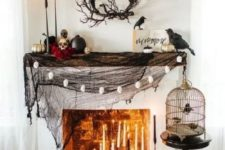 a scary Halloween mantel and fireplace with lots of candles, painted pumpkins, a branch wreath and blackbirds
