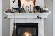 a spooky Halloween mantel with checked pumpkins, candles, dark tulle, bats and some witches' brew