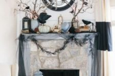 a spooky Halloween mantel with dark tulle, branches with blackbirds, pumpkins and a candle lantern