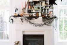a whimsical Halloween mantel with blackbirds and owls, stacks of books, black tulle and candles